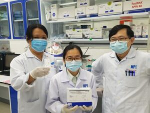 MP Biomedicals Diagnostics division's Research and Development team with their ASSURE(R) SARS-CoV-2 IgG/IgM Rapid Test kits. Two devices shown reflects positive IgG antibodies result (marked, on right) and a negative reading (unmarked, on left) From left: Ivy Teoh; Delynn Xu; Zee Hong Goh (Photo credit: MP Biomedicals)